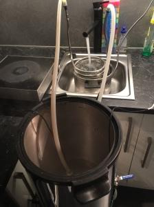 Flytter gyta til vasken og pøser på med kaldt vann for kjøling.